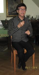 Mann sitzt auf einem Stuhl, Hände zu Gebärden erhoben