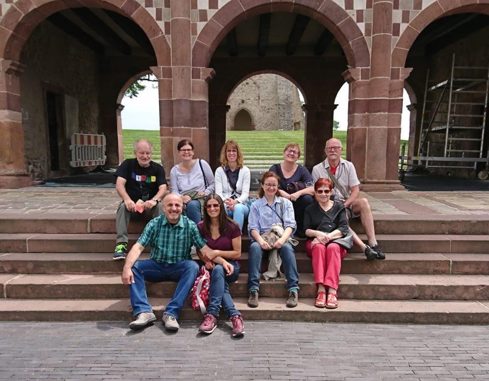 Teilnehmer sitzen auf Treppenstufen vor Torbögen