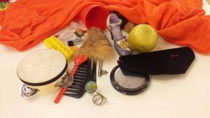 Gegenstände zum Ertasten halb unter einem Tuch verdeckt: Minitrommel, Kamm, Löffel, Legostein, goldener Ball, Spiegel, Minischuh und Murmeln