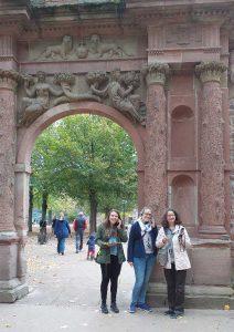 3 Frauen mit Audioguides stehen an einem steinernen Tor mit verzierten Säulen und Skulpturen