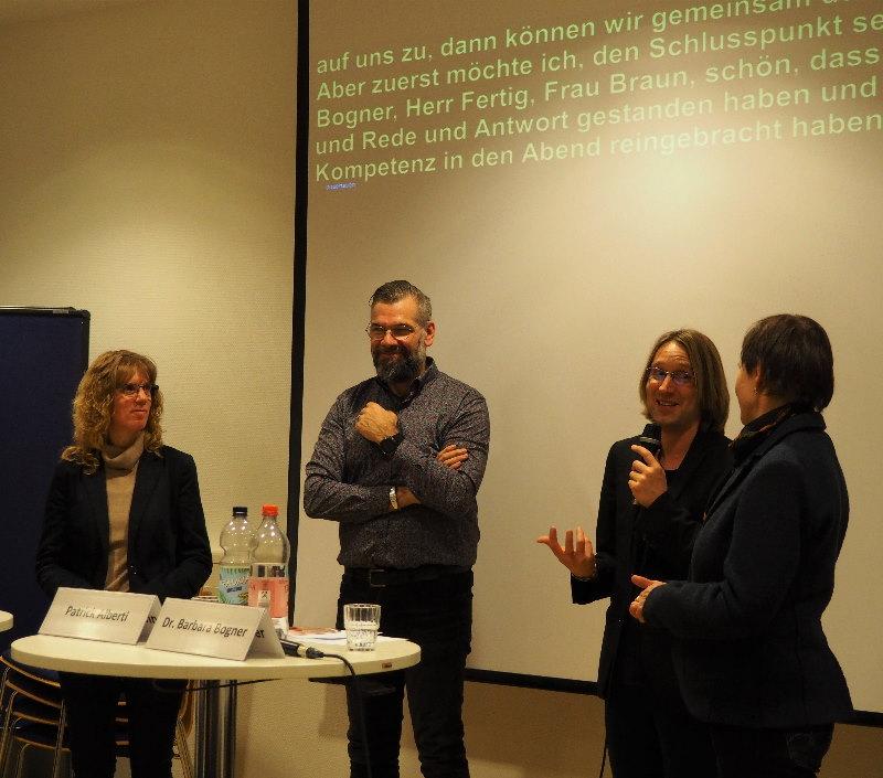 Das Bild zeigt die Teilnehmenden der Podiumsdiskussion mit Moderator Patrick Alberti, im Hintergrund Schriftdolmetschung am Beamer