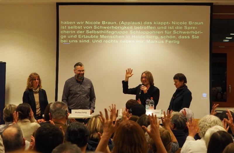Das Bild zeigt Publikum mit zum Applaus erhobenen Händen und im Hintergrund die Teilnehmer der Podiumsdiskussion
